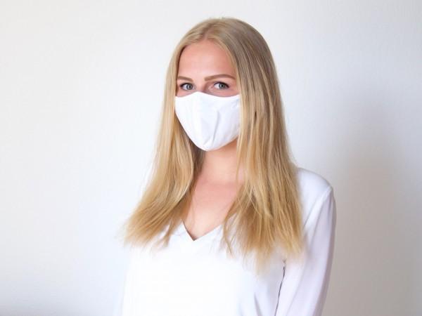Junge blonde Frau mit weißer Maske von Seidensticker und weißer Bluse Marke Seidensticker